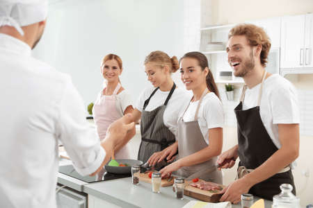 Group of people and male chef at cooking classes Stock Photo