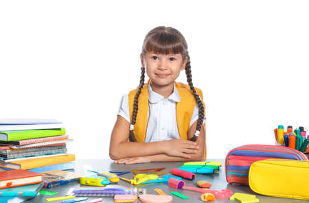 Schoolgirl at table with stationery against white background