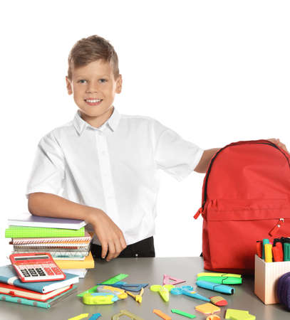 Schoolboy at table with stationery against white background
