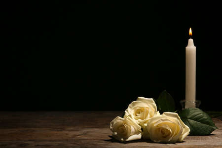 Beautiful white roses and candle on table against black background. Funeral symbol Фото со стока