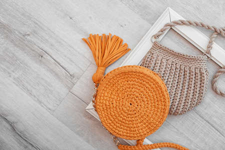 Knitted bags and space for design on wooden background, flat lay