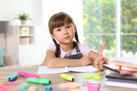 Little girl doing assignment at home. Stationery for school
