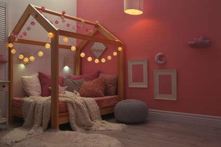 Interno della stanza del bambino con letto comodo e ghirlanda