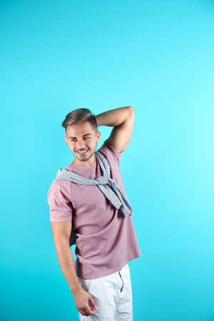 Young man with trendy hairstyle on color background Stock Photo