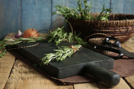 Wooden board with rosemary on table. Aromatic herbs