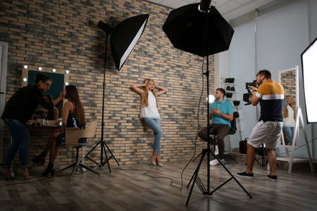 Professional team working with model in photo studio Stockfoto