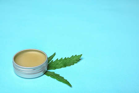 Jar with hemp lotion and space for text on color background Stock Photo