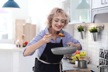 Professional female chef cooking vegetables in kitchen Stock Photo