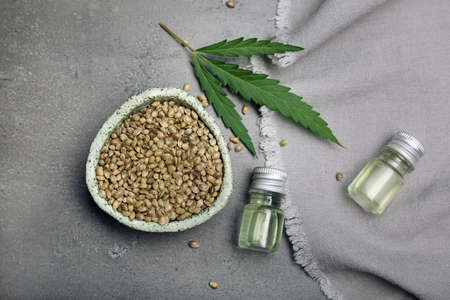Flat lay composition with hemp seeds and bottles of extract on grey background