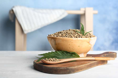 Bowl of hemp seeds on table against color background