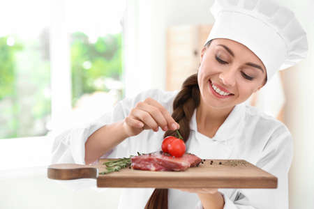 Professional female chef holding board with meat in kitchen