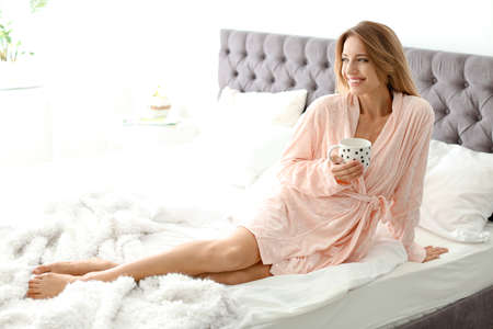 Beautiful young woman with cup of coffee sitting in bed at home. Lazy morning