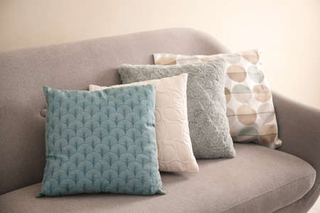 Different soft pillows on sofa in room