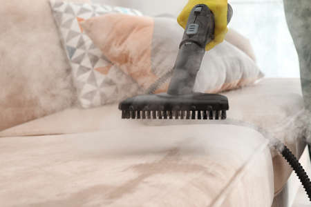 Janitor removing dirt from sofa with steam cleaner, closeup 스톡 콘텐츠
