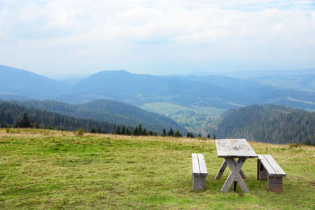 Picturesque landscape with wooden picnic table and mountain forest on background