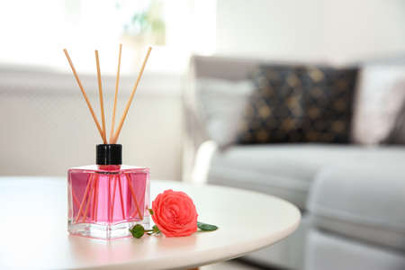 Aromatic reed parfume and rose on table indoors
