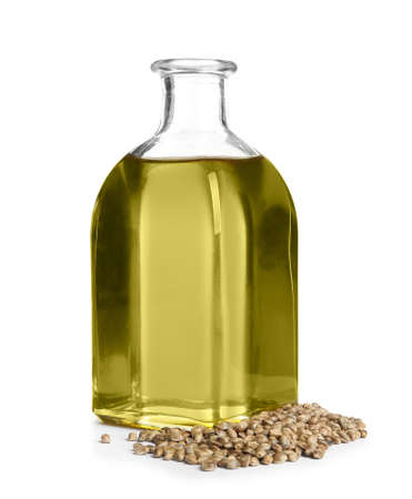 Bottle with hemp oil and seeds on white background