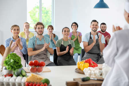 Group of people and female chef at cooking classes