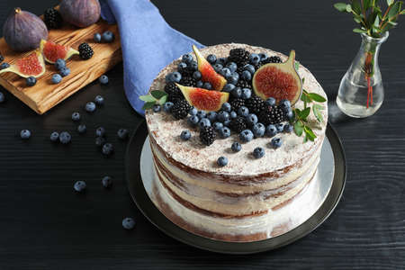 Delicious homemade cake with fresh berries served on dark wooden table