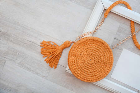 Flat lay composition with knitted bag and space for design on wooden background