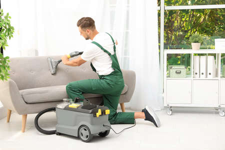Male janitor removing dirt from sofa with upholstery cleaner in room