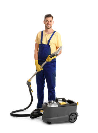 Male janitor with carpet cleaner on white background