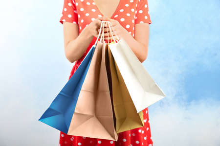 Woman holding paper shopping bags on color background