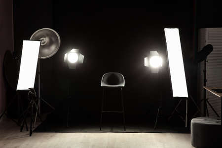 Interior of modern photo studio with chair and professional lighting equipment