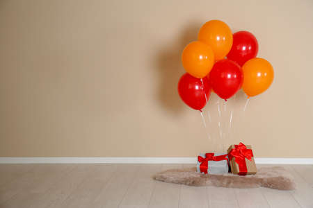 Bunch of bright balloons and gifts on floor against color wall. Space for text