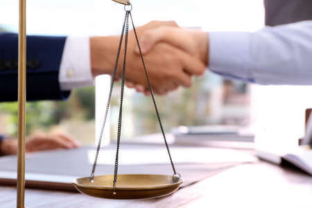 Scales of justice and blurred lawyer handshaking with client on background