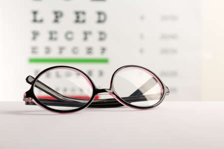 Glasses with corrective lenses on table against eye chart