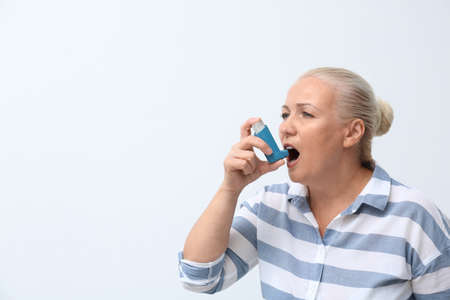 Woman using asthma inhaler on white background Stock Photo