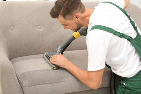 Male janitor removing dirt from sofa with upholstery cleaner indoors