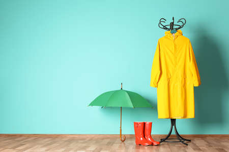 Umbrella, rain coat and boots near color wall with space for design Stockfoto