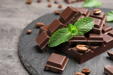 Pieces of dark chocolate with mint on slate plate