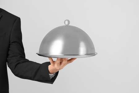 Waiter holding metal tray with lid on light background Banque d'images