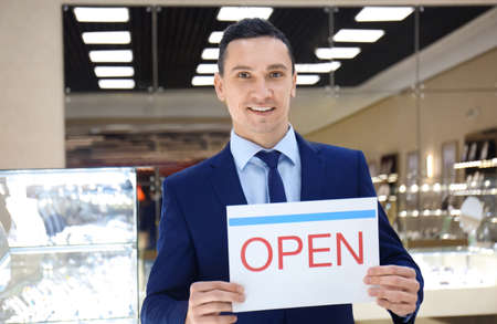Portrait of young man with OPEN sign in jewelry store. Small business owner Banco de Imagens