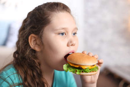 Overweight girl eating burger indoors Stock Photo
