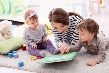 Niñera joven con lindos niños pequeños, en el interior