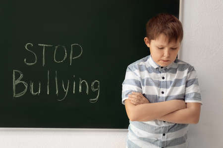 Little boy near chalkboard with words Stop bullying indoors Banco de Imagens