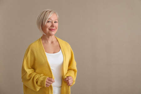 Portrait of beautiful mature woman on color background