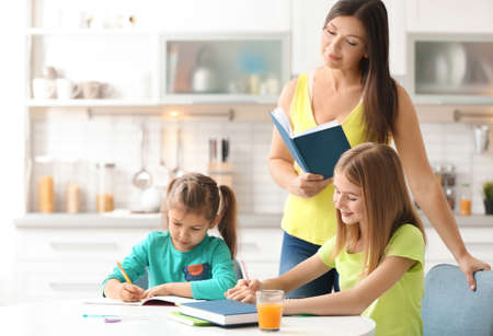 Cute little sisters doing homework with mother in kitchen