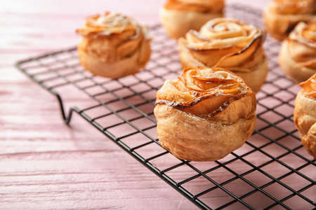 Cooling rack with apple roses from puff pastry on color wooden background, closeup
