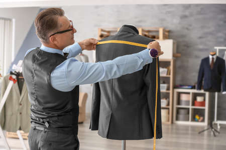 Tailor taking measurements of jacket on mannequin in atelier