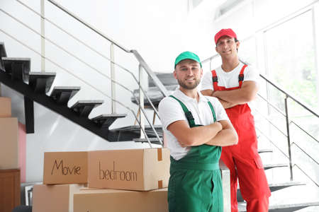 Portrait of male movers in uniform indoors