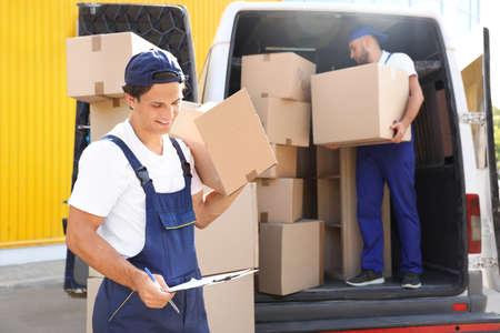 Mover mâle avec boîte et presse-papiers près de van à l'extérieur Banque d'images