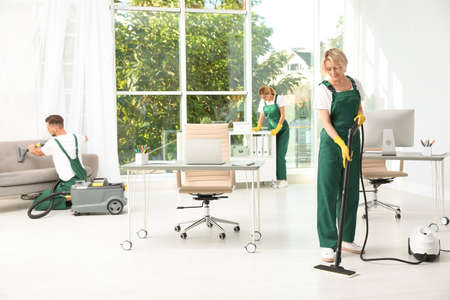 Team of janitors in uniform cleaning office Imagens - 107763499