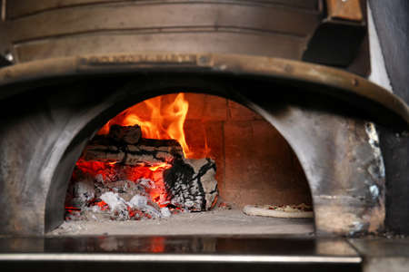 Oven with burning firewood and tasty pizza in restaurant kitchen