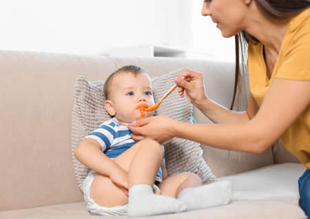 Woman feeding her child on couch indoors. Healthy baby food Archivio Fotografico
