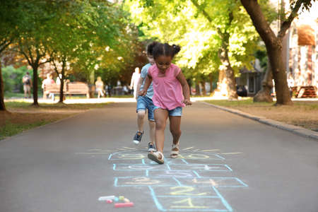 Little children playing hopscotch drawn with colorful chalk on asphalt